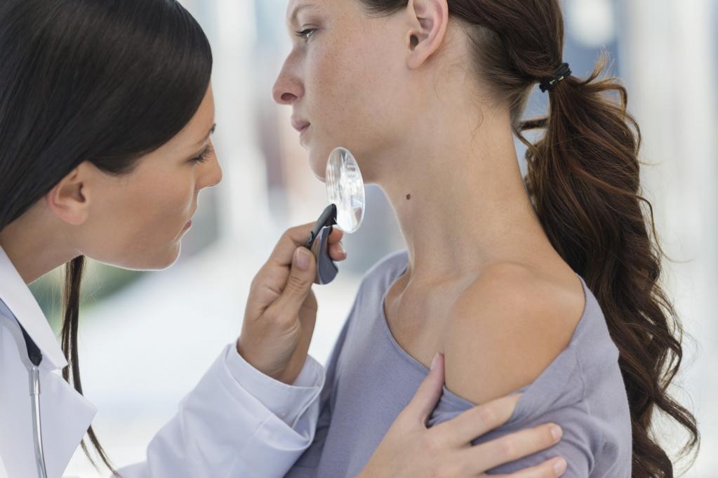 Дерматолог осматривает кожу у пациента